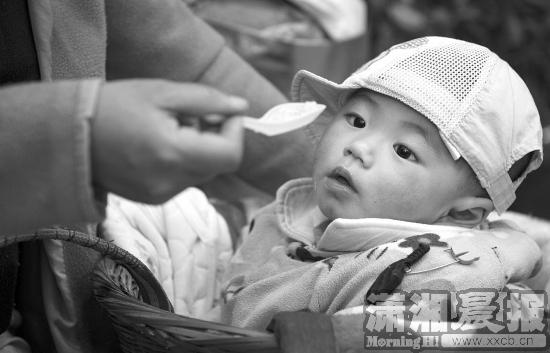 向艳萍给背篓里1岁多的儿子韩韩喂稀饭